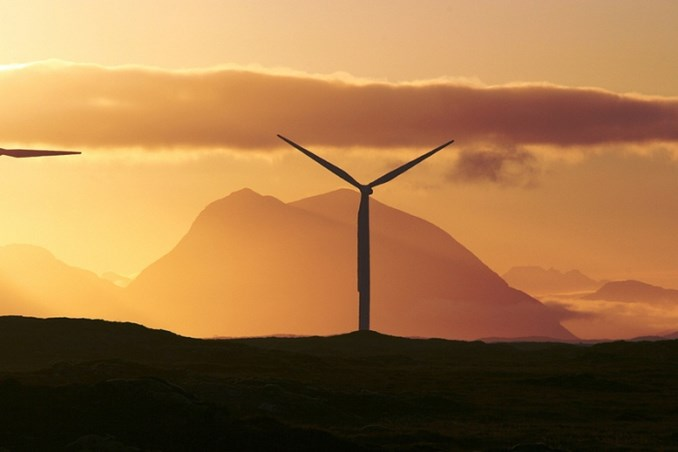 Wind turbine against orange sky